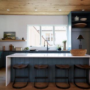 オースティンの広いコンテンポラリースタイルのおしゃれなキッチン (フラットパネル扉のキャビネット、クオーツストーンカウンター、白いキッチンパネル、無垢フローリング、白いキッチンカウンター、アンダーカウンターシンク、ターコイズのキャビネット、シルバーの調理設備、茶色い床) の写真