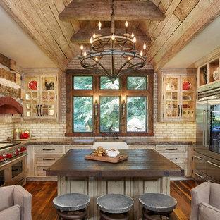 Bild på ett mellanstort rustikt brun brunt kök, med en rustik diskho, luckor med glaspanel, skåp i slitet trä, beige stänkskydd, stänkskydd i tegel, rostfria vitvaror, mellanmörkt trägolv, en köksö och träbänkskiva