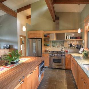 Modelo de cocina en L, clásica renovada, con fregadero bajoencimera, armarios estilo shaker, puertas de armario de madera oscura, salpicadero multicolor y electrodomésticos de acero inoxidable