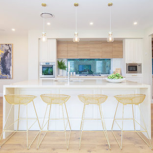 Contemporary eat-in kitchen in Sydney with an undermount sink, raised-panel cabinets, white cabinets, window splashback, stainless steel appliances, light hardwood floors, with island, beige floor and white benchtop.