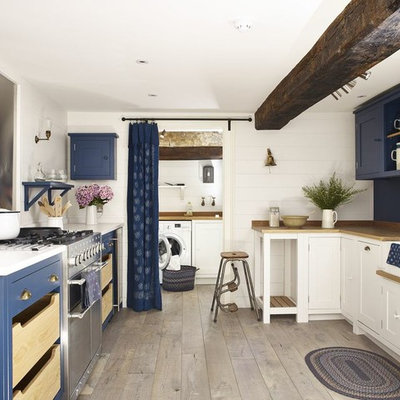 Beach style u-shaped medium tone wood floor and beige floor enclosed kitchen photo in Wiltshire with a farmhouse sink, blue cabinets, wood countertops, metallic backsplash, stainless steel appliances and no island