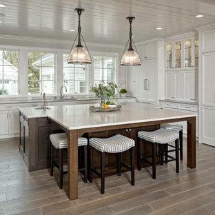 ミネアポリスの巨大なビーチスタイルのおしゃれなキッチン (アンダーカウンターシンク、フラットパネル扉のキャビネット、白いキャビネット、御影石カウンター、マルチカラーのキッチンパネル、石タイルのキッチンパネル、ラミネートの床、茶色い床、グレーのキッチンカウンター) の写真