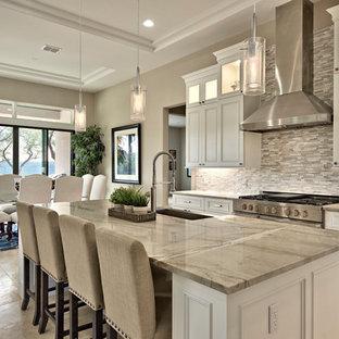 オースティンの大きい地中海スタイルのおしゃれなキッチン (アンダーカウンターシンク、ガラス扉のキャビネット、白いキャビネット、大理石カウンター、ガラスタイルのキッチンパネル、シルバーの調理設備、ライムストーンの床、マルチカラーの床) の写真