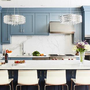 Idee per una cucina costiera di medie dimensioni con lavello sottopiano, ante in stile shaker, ante blu, top in marmo, paraspruzzi bianco, paraspruzzi in marmo, elettrodomestici in acciaio inossidabile, pavimento in legno massello medio, isola, top bianco e pavimento marrone
