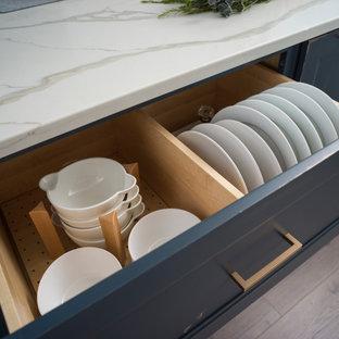 Bild på ett mellanstort lantligt vit vitt kök, med en rustik diskho, släta luckor, bänkskiva i kvartsit, vitt stänkskydd, stänkskydd i sten, rostfria vitvaror, mellanmörkt trägolv, en köksö, brunt golv och blå skåp