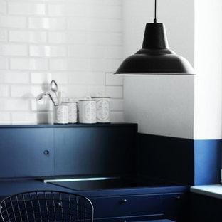 ロンドンの中サイズのインダストリアルスタイルのおしゃれなキッチン (シングルシンク、インセット扉のキャビネット、青いキャビネット、ラミネートカウンター、青いキッチンパネル、レンガのキッチンパネル、黒い調理設備、磁器タイルの床、青い床、青いキッチンカウンター) の写真