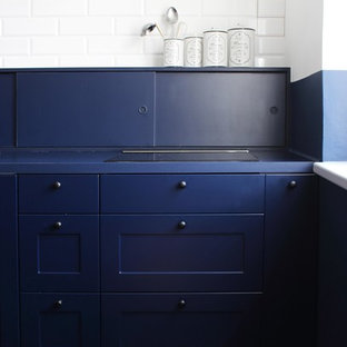 Design ideas for a medium sized urban galley open plan kitchen in London with a single-bowl sink, beaded cabinets, blue cabinets, laminate countertops, blue splashback, brick splashback, black appliances, porcelain flooring, an island, blue floors and blue worktops.