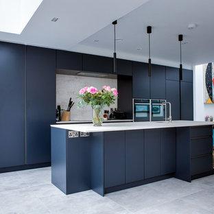 Offene, Zweizeilige, Mittelgroße Moderne Küche mit Einbauwaschbecken, flächenbündigen Schrankfronten, blauen Schränken, Quarzit-Arbeitsplatte, Küchenrückwand in Grau, Rückwand aus Stein, Küchengeräten aus Edelstahl, Porzellan-Bodenfliesen, Kücheninsel, grauem Boden und grauer Arbeitsplatte in Dublin