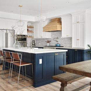 サンフランシスコの大きいビーチスタイルのおしゃれなキッチン (シェーカースタイル扉のキャビネット、グレーのキッチンパネル、シルバーの調理設備の、淡色無垢フローリング、エプロンフロントシンク、白いキャビネット、人工大理石カウンター、茶色い床、白いキッチンカウンター) の写真