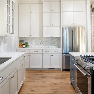 Ispirazione per una cucina classica di medie dimensioni con lavello a vasca singola, ante in stile shaker, ante bianche, top in quarzo composito, paraspruzzi bianco, paraspruzzi con piastrelle in pietra, elettrodomestici in acciaio inossidabile, isola e pavimento in legno massello medio