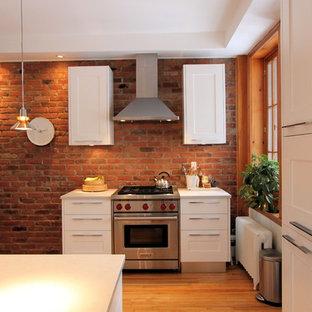 モントリオールの中くらいのコンテンポラリースタイルのおしゃれなキッチン (シェーカースタイル扉のキャビネット、白いキャビネット、人工大理石カウンター、マルチカラーのキッチンパネル、レンガのキッチンパネル、シルバーの調理設備、無垢フローリング) の写真