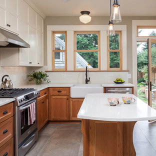 Photo of a mid-sized arts and crafts l-shaped separate kitchen in Portland with a farmhouse sink, medium wood cabinets, quartz benchtops, white splashback, ceramic splashback, stainless steel appliances, ceramic floors, with island, recessed-panel cabinets and grey floor.