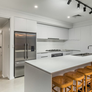 Design ideas for a contemporary l-shaped kitchen in Perth with a double-bowl sink, flat-panel cabinets, white cabinets, white splashback, stainless steel appliances, with island, beige floor and grey benchtop.