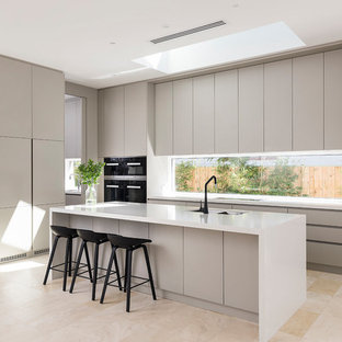 This is an example of a large contemporary galley open plan kitchen in Perth with an undermount sink, grey cabinets, quartz benchtops, window splashback, travertine floors, with island, beige floor, flat-panel cabinets and black appliances.