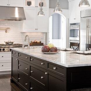 Foto di una cucina classica con elettrodomestici in acciaio inossidabile, top in granito, ante con riquadro incassato, ante bianche, paraspruzzi bianco, paraspruzzi con piastrelle diamantate e top bianco