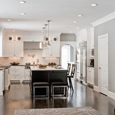 Elegant l-shaped kitchen photo in Boston with stainless steel appliances, a farmhouse sink, white cabinets, white backsplash and subway tile backsplash