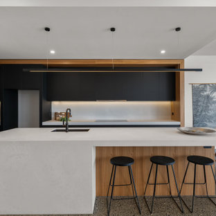 This is an example of a beach style galley open plan kitchen in Sunshine Coast with an undermount sink, flat-panel cabinets, black cabinets, white splashback, black appliances, terrazzo floors, with island, brown floor and white benchtop.