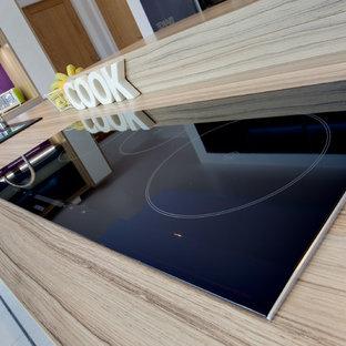 他の地域の大きいモダンスタイルのおしゃれなキッチン (ダブルシンク、フラットパネル扉のキャビネット、グレーのキャビネット、木材カウンター、ピンクのキッチンパネル、ガラス板のキッチンパネル、黒い調理設備、セラミックタイルの床) の写真