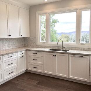 Inspiration för lantliga beige kök, med skåp i shakerstil, vita skåp, bänkskiva i kvartsit, grått stänkskydd, stänkskydd i marmor, rostfria vitvaror, mellanmörkt trägolv, en köksö och beiget golv