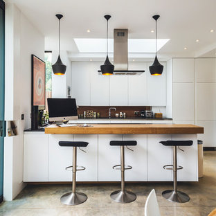 Design ideas for a medium sized contemporary u-shaped kitchen/diner in London with flat-panel cabinets, white cabinets, wood worktops, brown splashback, wood splashback, black appliances, a breakfast bar and beige worktops.