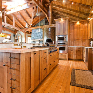 Craftsman kitchen ideas - Arts and crafts kitchen photo in Calgary with a farmhouse sink, shaker cabinets, medium tone wood cabinets, wood countertops, multicolored backsplash and stainless steel appliances