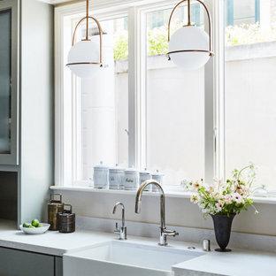 サンフランシスコの広いトランジショナルスタイルのおしゃれなキッチン (エプロンフロントシンク、フラットパネル扉のキャビネット、グレーのキャビネット、クオーツストーンカウンター、白いキッチンパネル、クオーツストーンのキッチンパネル、シルバーの調理設備、セラミックタイルの床、アイランドなし、グレーの床、白いキッチンカウンター) の写真