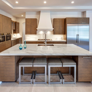 Inspiration for a large contemporary open plan kitchen in Essex with a built-in sink, flat-panel cabinets, medium wood cabinets, marble worktops, white splashback, marble splashback, stainless steel appliances, an island and beige floors.