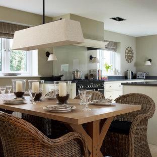 Foto på ett stort vintage kök, med en rustik diskho, luckor med profilerade fronter, skåp i ljust trä, bänkskiva i koppar, grönt stänkskydd, glaspanel som stänkskydd, svarta vitvaror, kalkstensgolv och en köksö