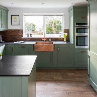 Exempel på ett mellanstort klassiskt kök, med en rustik diskho, skåp i shakerstil, gröna skåp, bänkskiva i kvarts, stänkskydd i metallkakel, linoleumgolv, en halv köksö, brunt stänkskydd, rostfria vitvaror och brunt golv