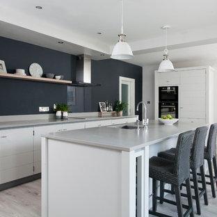 ダブリンの大きいトランジショナルスタイルのおしゃれなキッチン (フラットパネル扉のキャビネット、白いキャビネット、淡色無垢フローリング、グレーの床、アンダーカウンターシンク、黒い調理設備) の写真