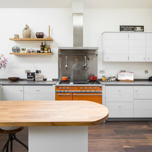Inspiration for a large industrial l-shaped kitchen in London with flat-panel cabinets, a breakfast bar, a submerged sink, white cabinets, white splashback, dark hardwood flooring, brown floors and grey worktops.