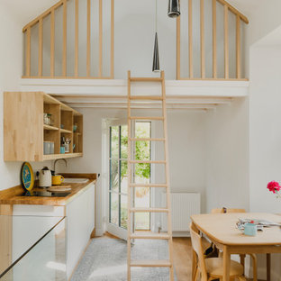 Inspiration for a nautical single-wall open plan kitchen in Other with a built-in sink, flat-panel cabinets, white cabinets, wood worktops, medium hardwood flooring, no island, brown floors and brown worktops.
