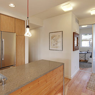 This is an example of a modern eat-in kitchen in Seattle with flat-panel cabinets, light wood cabinets, recycled glass benchtops, beige splashback, porcelain splashback, stainless steel appliances, light hardwood floors and with island.