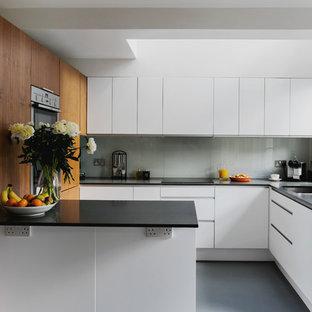 ロンドンのコンテンポラリースタイルのおしゃれなペニンシュラキッチン (アンダーカウンターシンク、フラットパネル扉のキャビネット、白いキャビネット、グレーのキッチンパネル、ガラス板のキッチンパネル、シルバーの調理設備、グレーの床、黒いキッチンカウンター) の写真