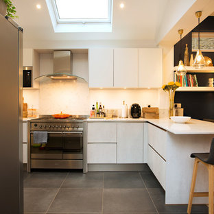 Small contemporary open plan kitchen in London with flat-panel cabinets, white cabinets, a breakfast bar and grey floors.