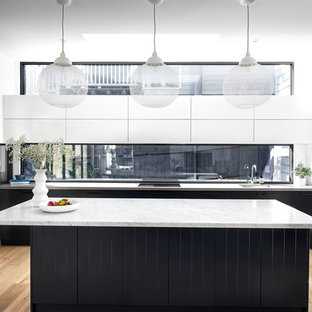 This is an example of a large contemporary l-shaped kitchen in Sydney with an undermount sink, marble benchtops, window splashback, light hardwood floors, with island, grey benchtop, flat-panel cabinets, black cabinets, stainless steel appliances and beige floor.