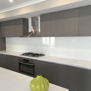 Inredning av ett modernt mellanstort kök, med en trippel diskho, luckor med upphöjd panel, skåp i mellenmörkt trä, bänkskiva i kvarts, vitt stänkskydd, glaspanel som stänkskydd, rostfria vitvaror och en köksö