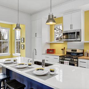Immagine di una cucina abitabile design di medie dimensioni con lavello sottopiano, ante lisce, ante bianche, top in quarzo composito, elettrodomestici in acciaio inossidabile, parquet scuro e isola