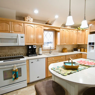 This is an example of a mid-sized traditional l-shaped kitchen pantry in Chicago with an undermount sink, raised-panel cabinets, light wood cabinets, quartz benchtops, multi-coloured splashback, travertine splashback, white appliances, vinyl floors, with island, beige floor and beige benchtop.