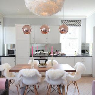ロンドンのコンテンポラリースタイルのおしゃれなキッチン (落し込みパネル扉のキャビネット、白いキャビネット、メタリックのキッチンパネル、ミラータイルのキッチンパネル、シルバーの調理設備、アイランドなし) の写真