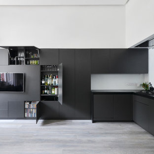 Small contemporary open concept kitchen pictures - Open concept kitchen - small contemporary l-shaped light wood floor and gray floor open concept kitchen idea in London with a double-bowl sink, flat-panel cabinets, black cabinets, no island and black countertops