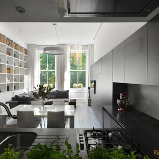 Small contemporary l-shaped open plan kitchen in London with a double-bowl sink, flat-panel cabinets, black cabinets, no island, grey floors and black worktops.