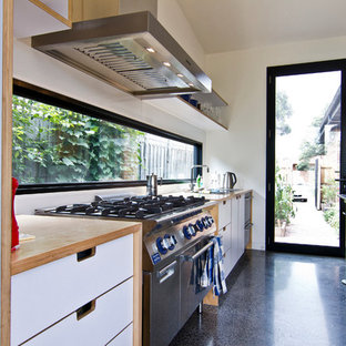 Inspiration for a large industrial galley eat-in kitchen in Melbourne with a double-bowl sink, flat-panel cabinets, white cabinets, wood benchtops, white splashback, glass sheet splashback, stainless steel appliances, concrete floors and with island.