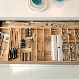 Idéer för ett litet modernt l-kök, med vitt stänkskydd, glaspanel som stänkskydd, klinkergolv i keramik, skåp i ljust trä och rostfria vitvaror