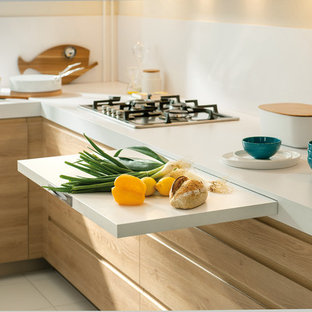 This is an example of a small contemporary l-shaped kitchen in London with white splashback, stainless steel appliances, ceramic flooring, light wood cabinets and glass sheet splashback.