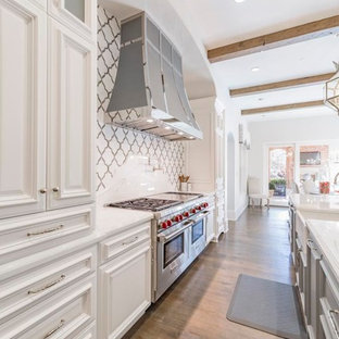 Photo of an expansive transitional l-shaped eat-in kitchen in Dallas with a farmhouse sink, raised-panel cabinets, white cabinets, marble benchtops, multi-coloured splashback, stone tile splashback, stainless steel appliances, dark hardwood floors, multiple islands and brown floor.