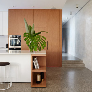 Design ideas for a contemporary galley kitchen in Sydney with flat-panel cabinets, medium wood cabinets, concrete floors, with island, grey floor and white benchtop.