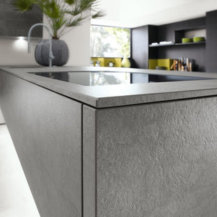 Mid-sized modern l-shaped open plan kitchen in Miami with an integrated sink, flat-panel cabinets, grey cabinets, solid surface benchtops, grey splashback, glass sheet splashback, panelled appliances, linoleum floors and a peninsula.