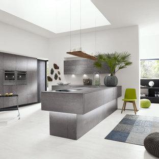 Создайте стильный интерьер: угловая кухня среднего размера в стиле модернизм с обеденным столом, монолитной раковиной, плоскими фасадами, серыми фасадами, столешницей из бетона, техникой из нержавеющей стали, полом из ламината, полуостровом, серым фартуком и фартуком из стекла - последний тренд