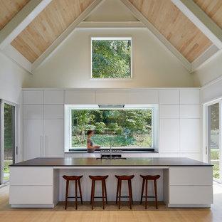 Modelo de cocina marinera con fregadero bajoencimera, armarios con paneles lisos, puertas de armario blancas, salpicadero de vidrio, suelo de madera clara, una isla y suelo beige